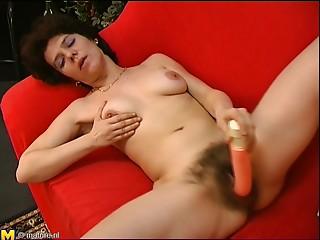 Older Carmen masturbates her bushy snatch and sucks a unyielding cock