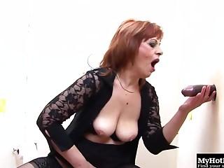 Redhead elder slag fingers her cunt and sucks on a gloryhole rod