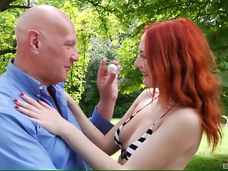 Curvaceous redhead enjoys the doggy drilling on the green grass