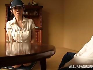 Mature Asian woman gives a guy a tit job and handjob